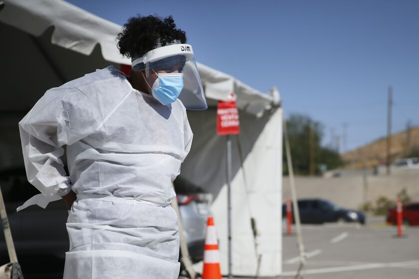 FILE - In this Oct. 26,2020, file photo, a medical worker stands at a COVID-19 state drive-thru testing site at UTEP, in El Paso, Texas. The U.S. has recorded about 10.3 million confirmed infections, with new cases soaring to all-time highs of well over 120,000 per day over the past week. (Briana Sanchez/The El Paso Times via AP, File)