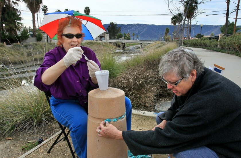 """Artists from Lake Elsinore's """"Studio 395"""" install mosaic tiles on safety bollards along the Lake Elsinore Riverwalk earlier this month. Nanci McGraw, left, applies quick-setting cement to a tile as Grace Sandlin, right, installs a tile."""