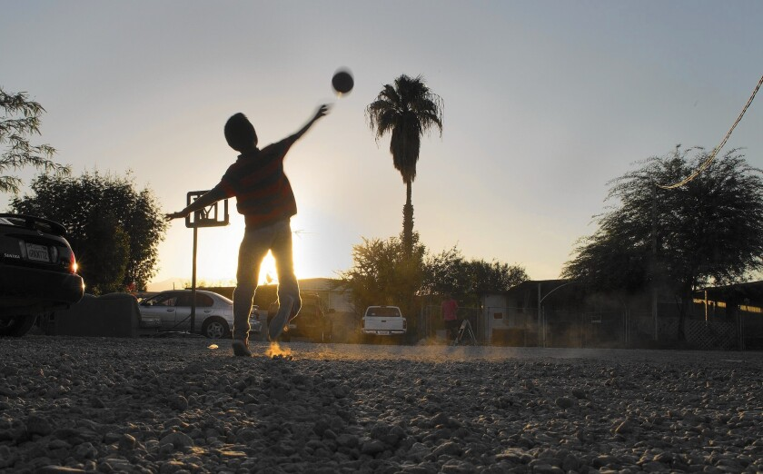 At St. Anthony's trailer park in Mecca, the nonprofit Pueblo Unido stepped in as owner to make improvements, but residents are frustrated with the slow progress. Above, Aaron Gonzalez, 11, tosses a football.