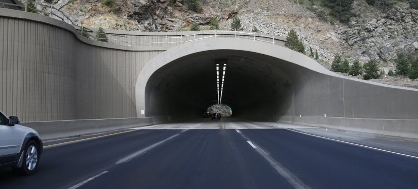 In this Saturday, Aug. 8, 2015, photograph taken near Idaho Springs, Colo., traffic flows through one of the newly-reconstructed twin tunnels along Interstate 70. Voter-sanctioned tax limits are threatening the state's growth, which depends on a functioning road system that has become crippled unde