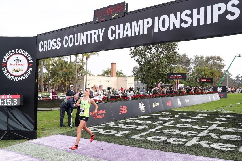 Sage Creek's Skyler Wallace crosses the finish line in the Foot Locker Nationals at Balboa Park's Morley Field.
