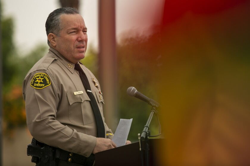 Los Angeles County Sheriff Alex Villanueva speaks at a lectern during a press conference
