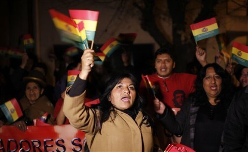 Supporters of Bolivia's President Evo Morales shout and wave Bolivian flags outside France's embassy as they protest in La Paz, Bolivia, Tuesday, July 2, 2013. Bolivia's Foreign Minister David Choquehuanca says the plane bringing President Evo Morales home from Russia was rerouted to Austria after France and Portugal refused to let it to cross their airspace because of suspicions that NSA leaker Edward Snowden was on board. Officials in both Austria and Bolivia said that Snowden was not on the p