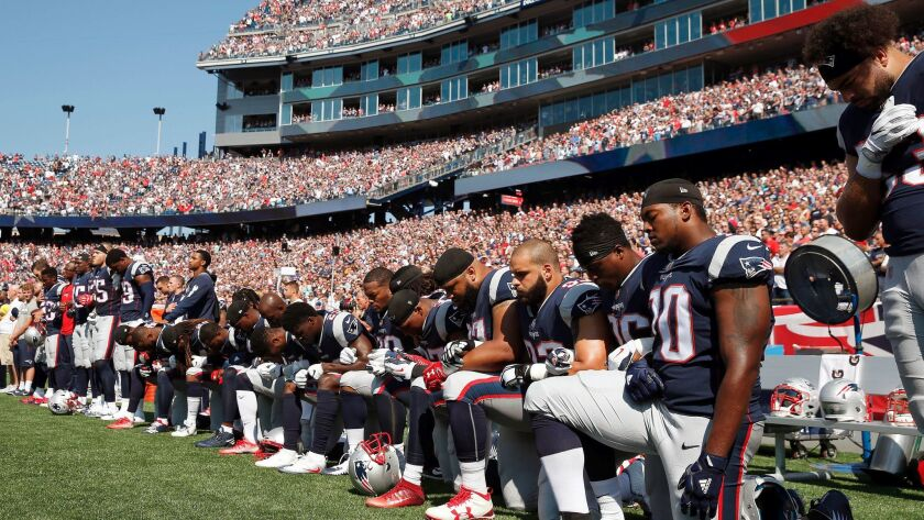 Several New England Patriots players kneel during the national anthem before an NFL football game ag