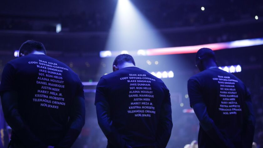 Players wear T-shirts bearing the names of the 12 victims killed in Wednesday night's shooting at a