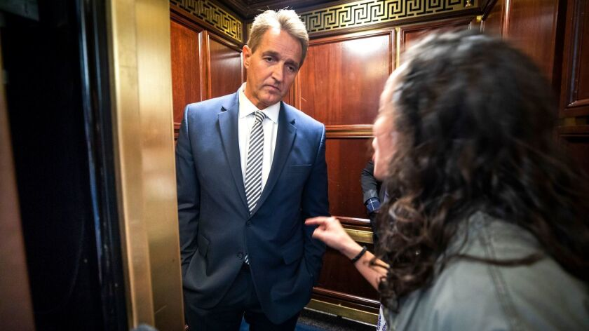 A woman who said she is a survivor of a sexual assault confronts Senator Arizona Jeff Flake (R-AZ) in an elevator after Flake announced that he would vote to confirm Supreme Court nominee Brett Kavanaugh in the Russell Senate Office Building in Washington on Sept. 28.