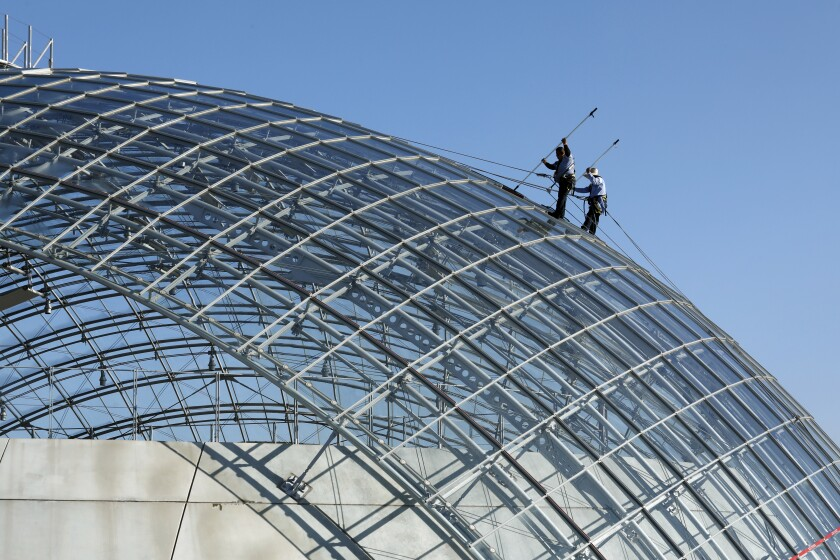 Window washers Mario Guzman, left, and Jesus Garcia, right, clean the dome of the Academy Museum of Motion Pictures.