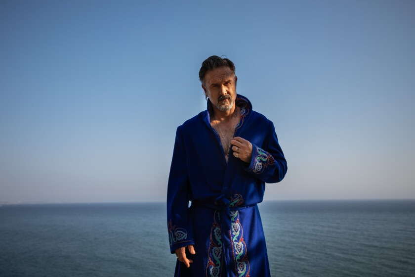 David Arquette is photographed in a vintage robe, channeling a wrestler and possibly Elvis, next to the Pacific Ocean.