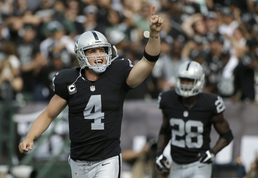 Oakland Raiders quarterback Derek Carr (4) reacts after throwing a touchdown pass to wide receiver Michael Crabtree during the first half of an NFL football game against the New York Jets in Oakland, Calif., Sunday, Nov. 1, 2015. (AP Photo/Marcio Jose Sanchez)