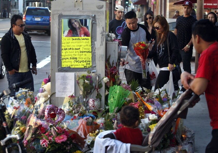 Spectators look over a memorial for Kim Pham, who was beaten to death outside a nightclub in Santa Ana last month.