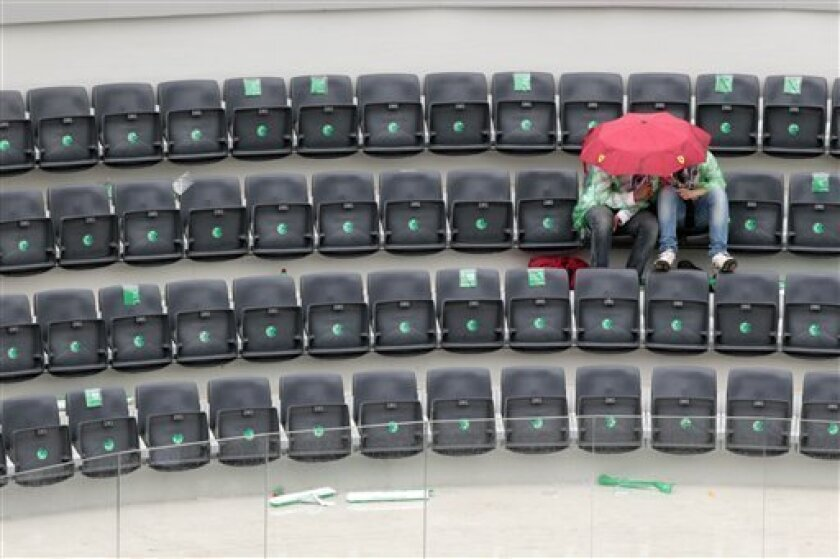People take shelter from the rain as the final match of the Rome Masters tennis tournament between Rafael Nadal and David Ferrer was suspended due to rain, in Rome, Sunday, May 2, 2010. (AP Photo/Alessandra Tarantino)