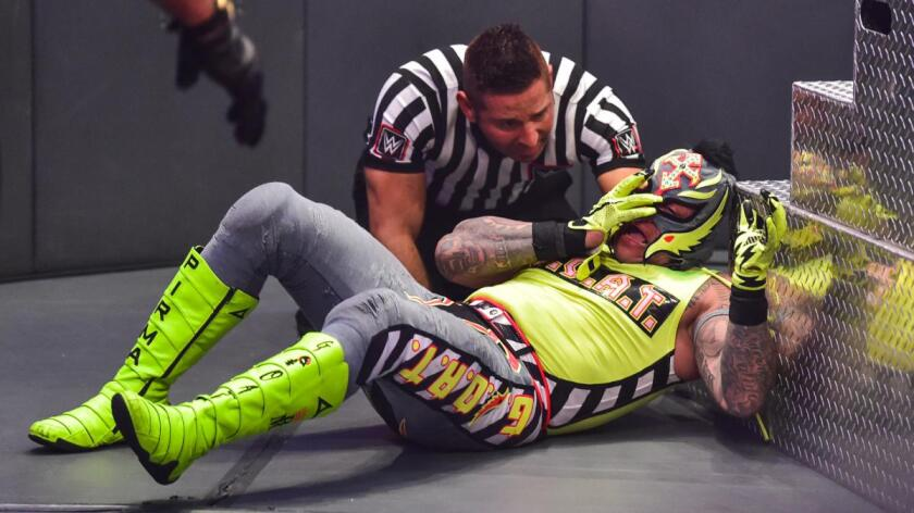 The ref checks on Rey Mysterio, who hopes to keep his eye in place.