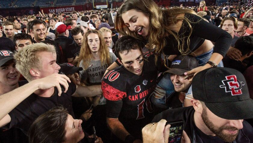 San Diego State quarterback Christian Chapman is swarmed by SDSU fans following the Aztecs' 20-17 home win over Stanford.
