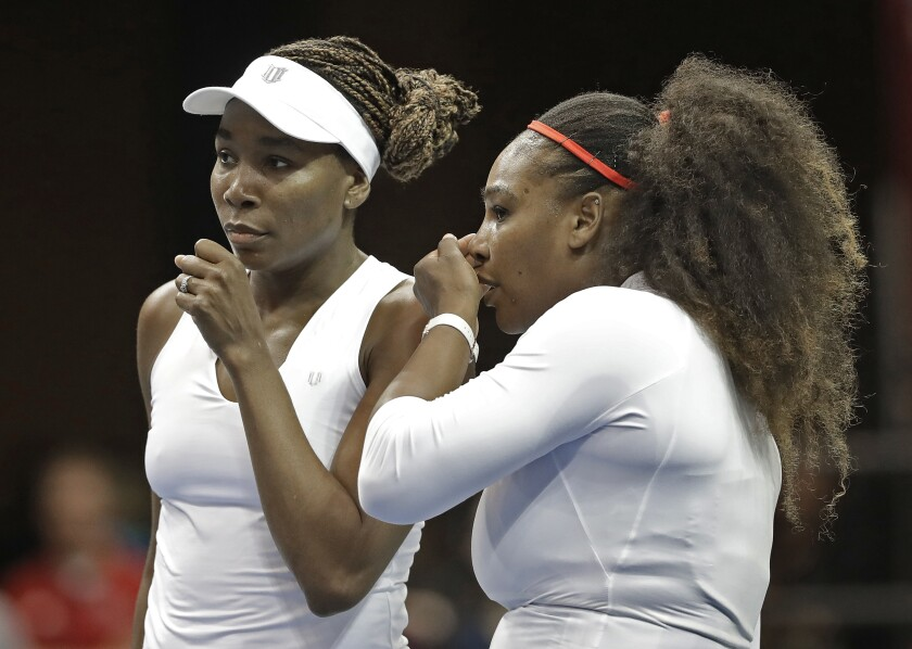FILE - In this Sunday, Feb. 11, 2018, file photo, USA's Venus Williams, left, and Serena Williams, right, talk between points in their doubles match against Netherlands' Leslie Herkhove and Demi Schuurs in the first round of Fed Cup tennis competition in Asheville, N.C. The siblings meet each other for the 31st time when they take the court at a WTA tournament in Kentucky on Thursday, Aug. 13, 2020. (AP Photo/Chuck Burton, File)