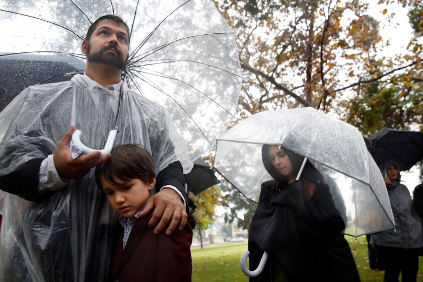 Dev Kumar, with son William and daughter Beatrice, stands during a ceremony to remember the 1,457 people cremated in 2016 in Los Angeles County whose remains have gone unclaimed for the past three years.