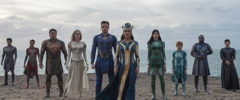 """A line of superheroes standing on the beach in the movie """"Eternals."""""""