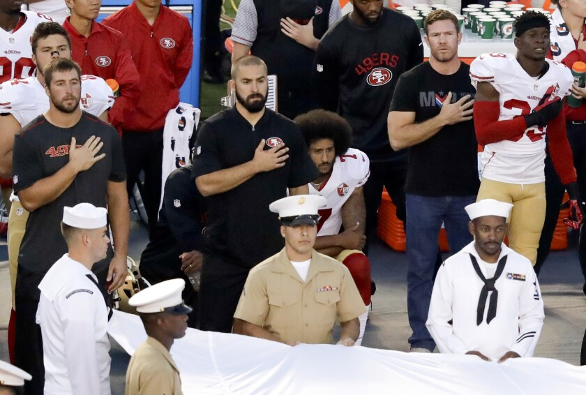 San Francisco 49ers quarterback Colin Kaepernick, center, refuses to stand during the national anthem before the team's NFL preseason football game against the San Diego Chargers on Thursday in San Diego.