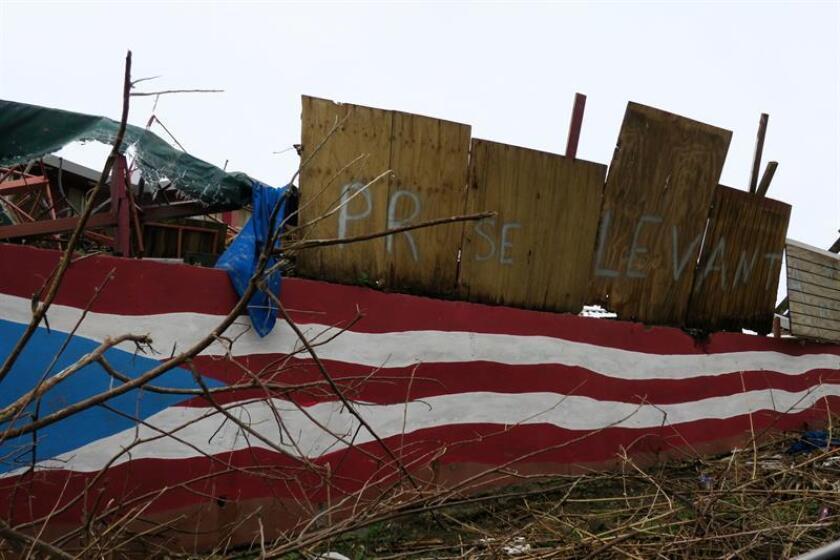 """Vista de un tablón de madera que reza """"PR Se Levanta"""", lema usado por puertorriqueños tras el paso del huracán María. EFE/Archivo"""