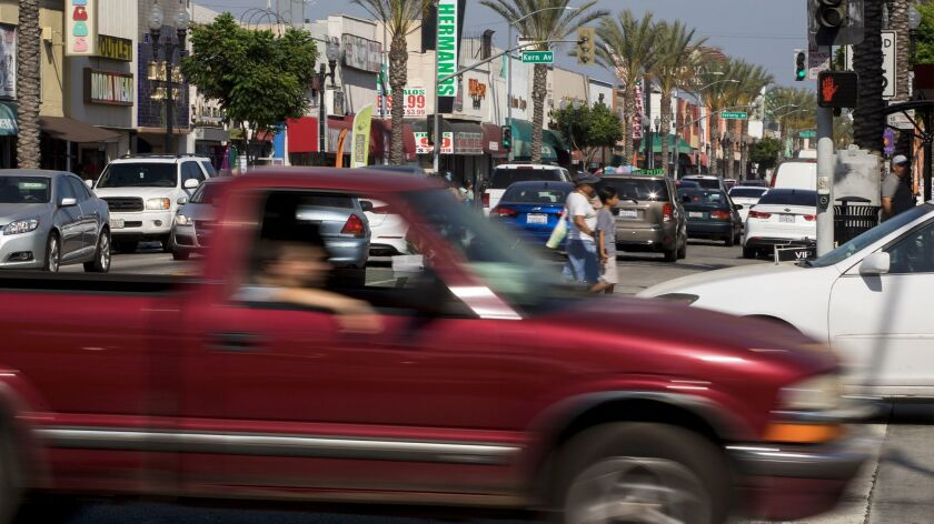 Whittier Boulevard at Arizona Avenue is jammed with traffic and pedestrians crossing the street.