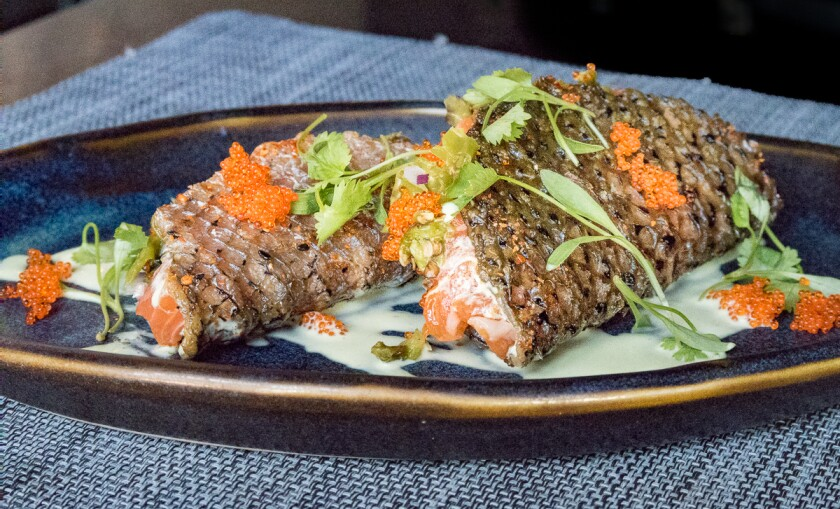 """The fish tacos with salmon-belly tartare, tobiko and smoked shishito peppers, in which the """"shells"""" are actually fried salmon skins, at the Black Sheep."""