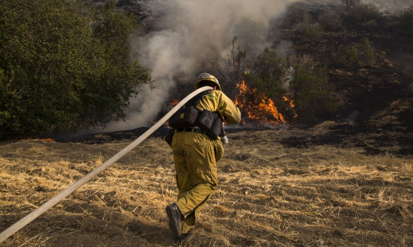 Firefighter battles flames in Calabasas and West Hills areas.