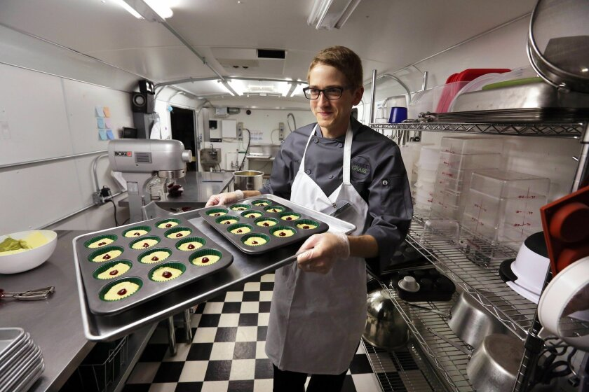 FILE - In this June 19, 2014, file photo, chef Alex Tretter carries a tray of cannabis-infused peanut butter and jelly cups to the oven for baking at Sweet Grass Kitchen, a well-established Denver-based gourmet marijuana edibles bakery which sells its confections to retail outlets throughout the st