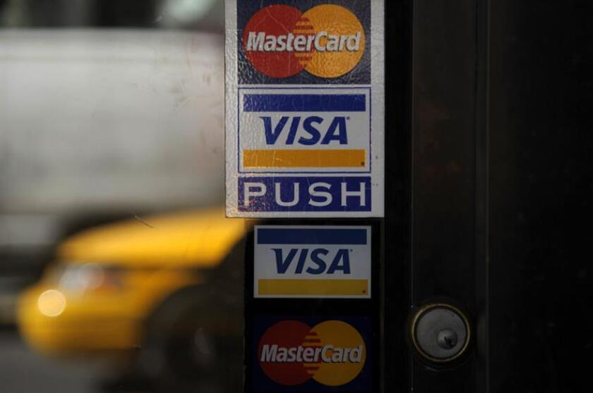 The Visa and Mastercard logo are displayed in store fronts in New York City, New York. EFE/Archivo