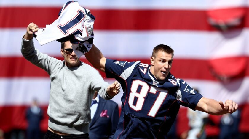 The Patriots' Rob Gronkowski steals Tom Brady's jersey before the opening day game between the Boston Red Sox and the Pittsburgh Pirates on April 3.