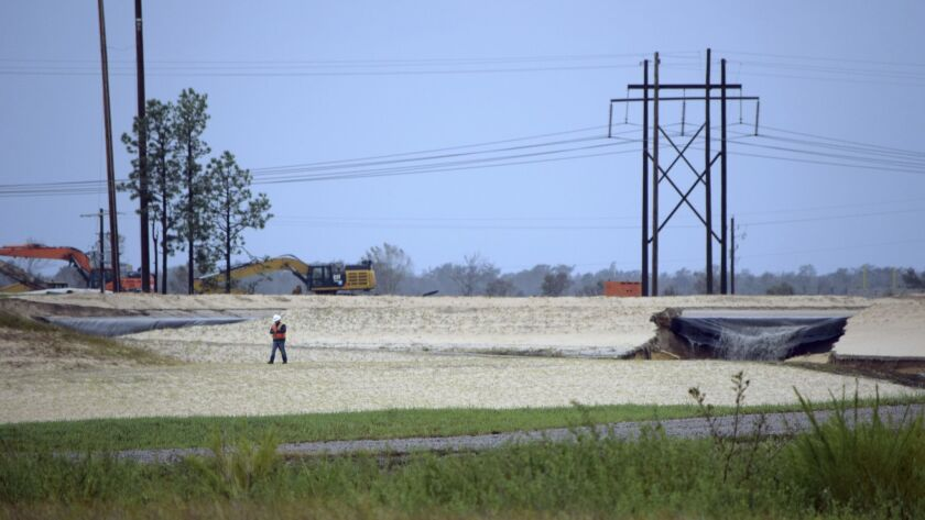 In this Sept. 16 photo released by Cape Fear River Watch, graywater containing coal ash flows from a ruptured landfill at the L.V. Sutton Power Station in Wilmington, N.C., toward Sutton Lake, near the Cape Fear River.