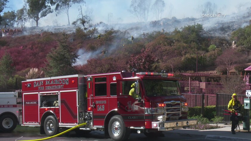 Crews work to douse a brush fire in San Marcos