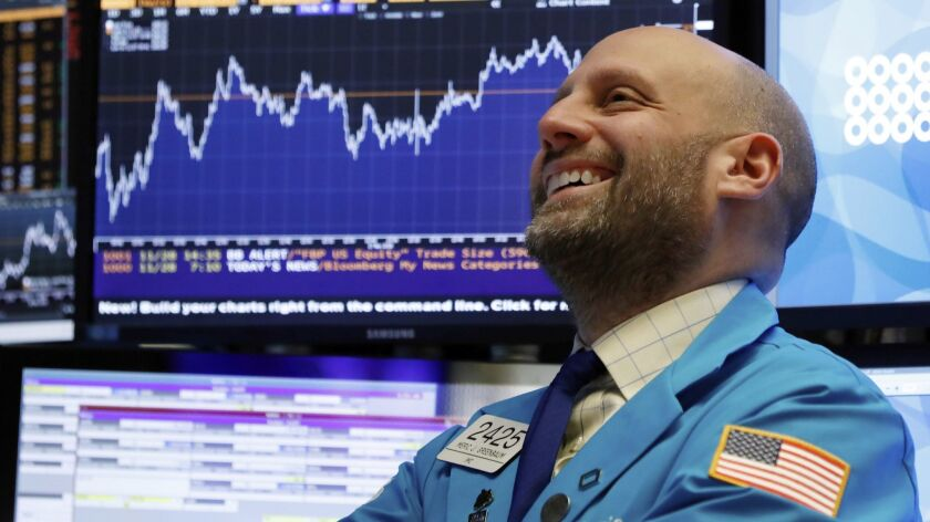 Specialist Meric Greenbaum smiles as he works on the floor of the New York Stock Exchange near the close of trading Wednesday.