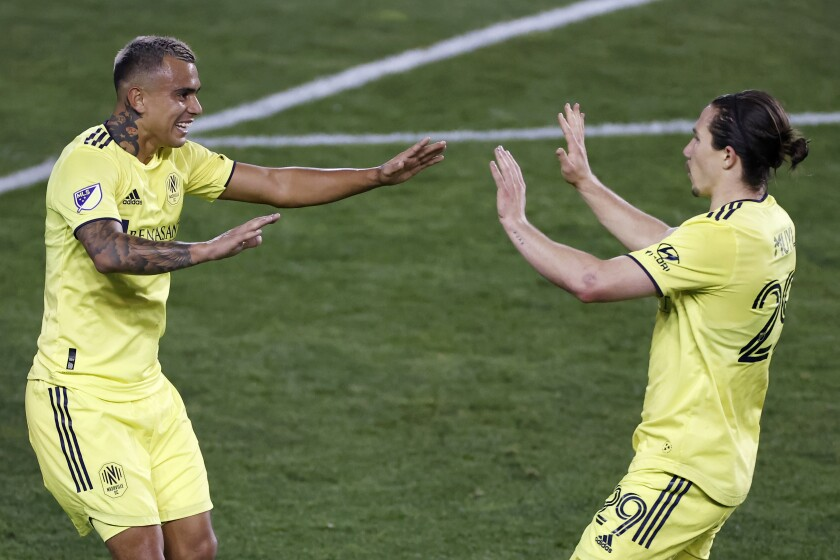 Nashville SC midfielder Randall Leal, left, is congratulated by Alex Muyl after scoring a goal during the first half of the team's MLS soccer match against the Montreal Impact, Tuesday, Oct. 27, 2020, in Harrison, N.J. (AP Photo/Adam Hunger)