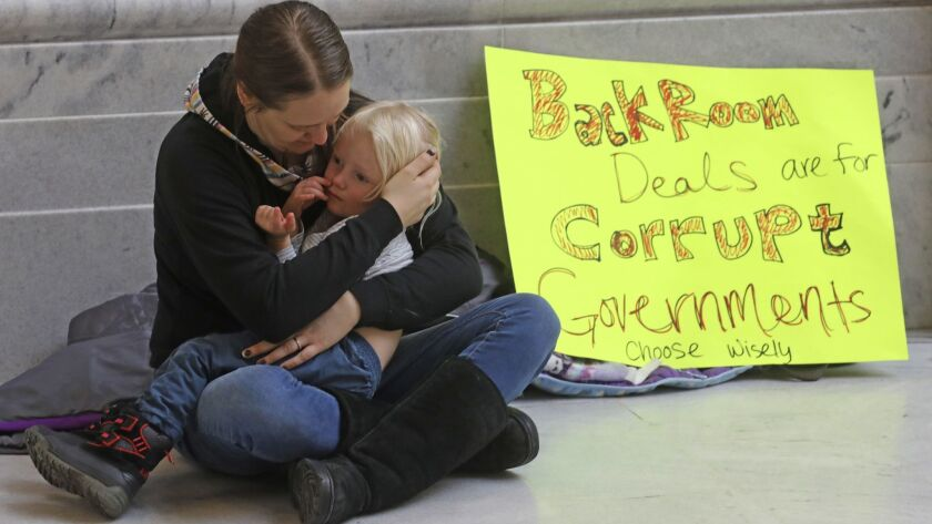 Letesha Case holds her daughter Aurora Case, 2, as they sit next to their sign Monday Dec. 3, 2018,