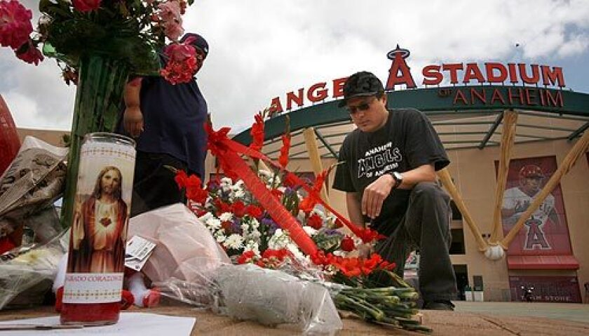 Robert Vargas, left, and Jason Lozano were among the many fans who stopped at Angel Stadium to leave flowers and remember pitcher Nick Adenhart. More photos >>>