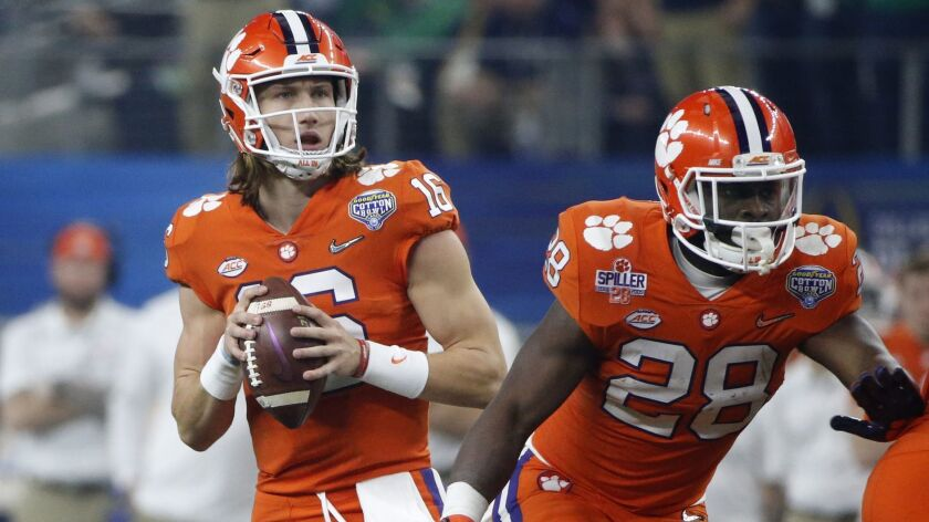 Clemson quarterback Trevor Lawrence (16) drops back to pass as running back Tavien Feaster (28) defe