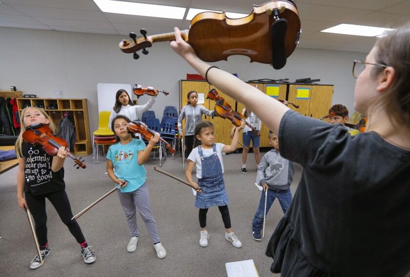 At the after school violin class at Conway Elementary School instructor Isabel Friedrich, 18, holds her violin in the air as her students follow to place the instruments in playing position for practice.