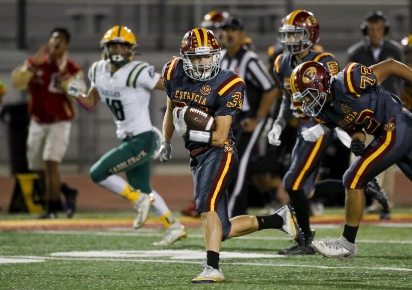 Estancia's Andrew Coyotzi (34) breaks into the secondary and heads for the end zone for a touchdown.