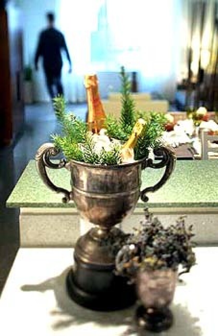 Bottles of Champagne ice up with sprigs of winter greenery in an antique trophy bucket that flaunts its age in unpolished splendor. In the foreground, a smaller vase holds black privet berry.