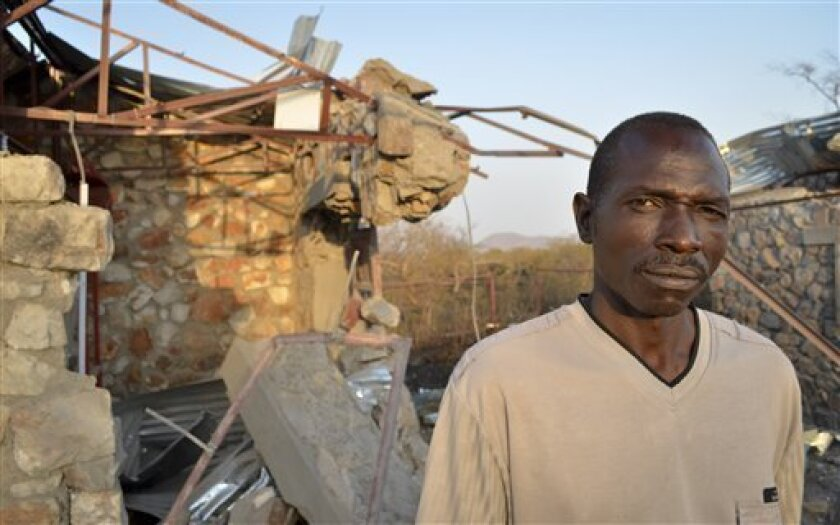 In this photo taken Wednesday, Feb. 1, 2012, school Pastor Zachariah Boulus stands next to a building in the compound of the Heiban Bible College, following a bombing on Wednesday, at the school which was built by Samaritan's Purse, a North Carolina-based aid group, in Heiban, Southern Kordofan, Sudan. Sudan's military bombed the Bible school built by a U.S. Christian aid group, prompting students and teachers at the school to run for their lives in the Nuba Mountains of South Kordofan state and the U.S. ambassador to the United Nations condemned the attack. (AP Photo/Ryan Boyette)