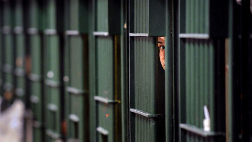 An inmate peeks through the bars at the restrictive housing unit, formerly known as solitary confinement, at the Men's Central Jail in Los Angeles on June 2, 2016.