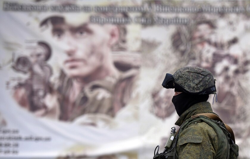 A Russian soldier stands in front of a recruitment poster for the Ukrainian armed forces Thursday near a surrounded Ukrainian military unit in the Crimean town of Perevalnoye.