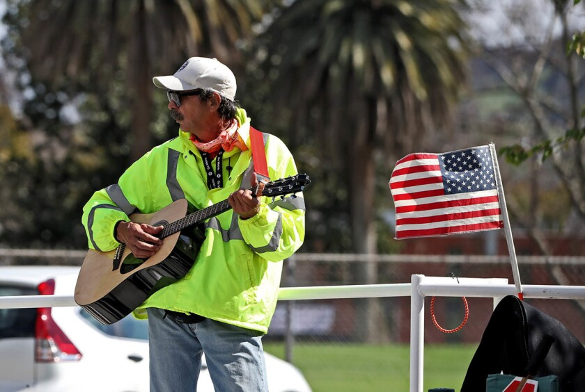 A photo taken on March 7, 2019, of George Contreras playing a guitar while working as a crossing guard at Walt Disney Elementary School.