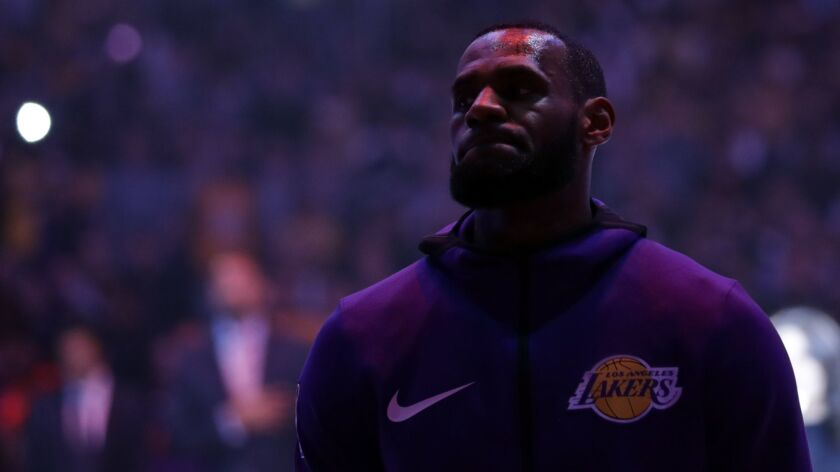 Los Angeles Lakers' LeBron James listens to the national anthem before an NBA basketball game agains