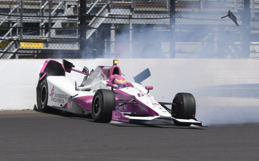 Pippa Mann, of England, hits the wall in the fourth turn during the final practice session for the Indianapolis 500 auto race at Indianapolis Motor Speedway in Indianapolis, Friday, May 27, 2016. (AP Photo/Larry Drake)