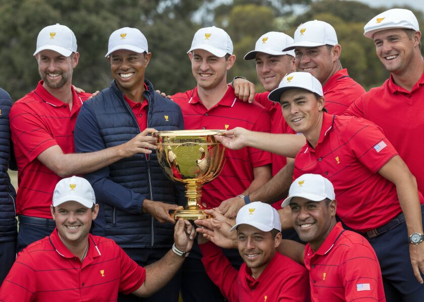U.S. team captain Tiger Woods and his teammates pose with the Presidents Cup after their win over the International team on Dec. 15.