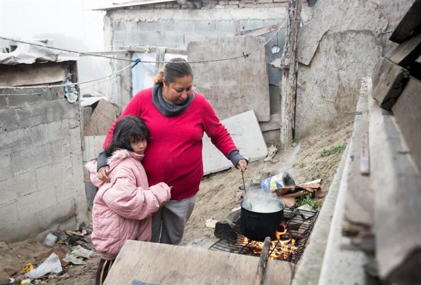 Fotografía de archivo del 17 de enero de 2018, que muestra a una mujer con su hija en un asentamiento irregular en la Ciudad de Saltillo, Coahuila (México). América Latina es la región más desigual del mundo en términos de ingreso y el poder se aprovecha de la pobreza para acrecentar el clientelismo existente, especialmente en periodos electorales, alertó hoy Oxfam. EFE/ARCHIVO