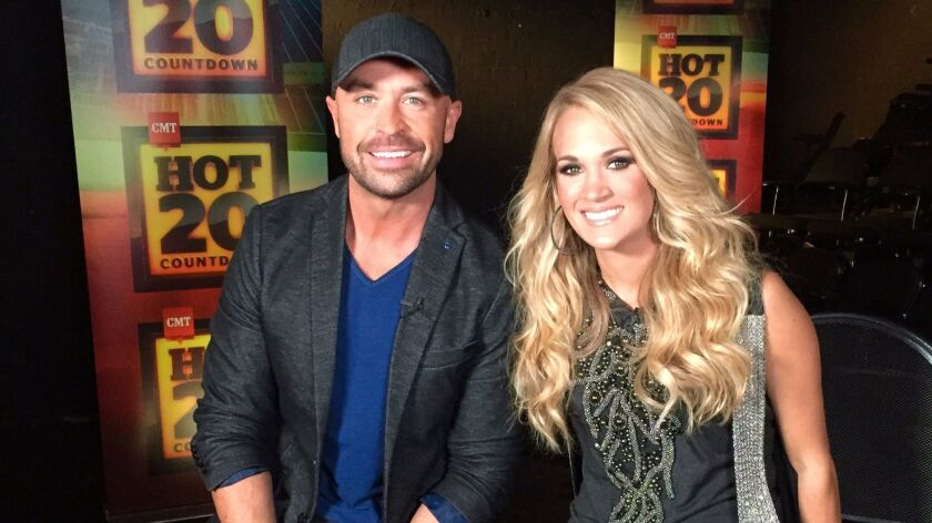 """Cody Alan, host of """"CMT Hot 20 Countdown,"""" with Carrie Underwood."""
