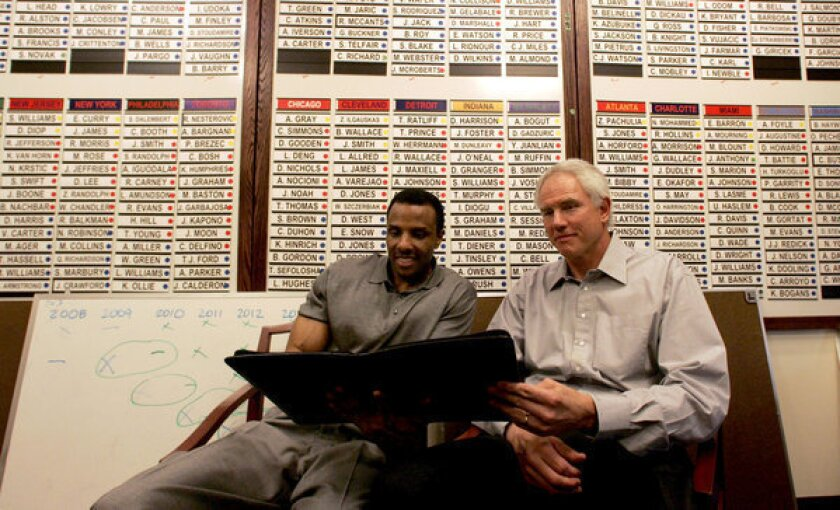 Ronnie Lester and Lakers GM Mitch Kupchak work below a roster board in Kupchak's office in 2008.