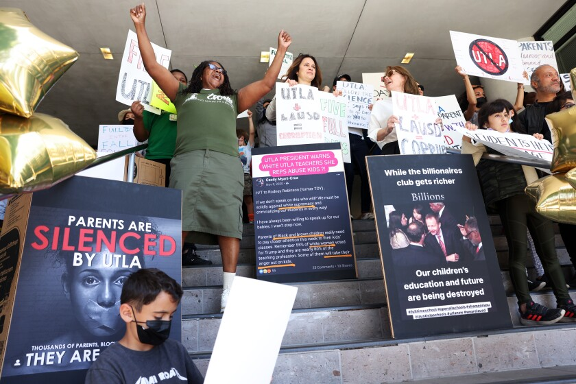 People hold signs during a rally calling for L.A. schools to reopen fully.