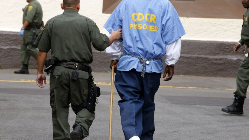 SAN QUENTIN, CA, APRIL 28, 2015: A death row inmate with a cane is escorted across the yard away fr